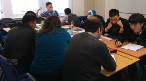 students of different nationalities sit around a table in a classroom. They have pens and notebooks and are holding discussions with each other.