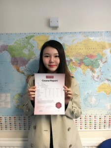 student Renee holds up her certificate