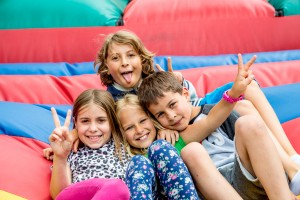 4 young students pose on a bouncy castle