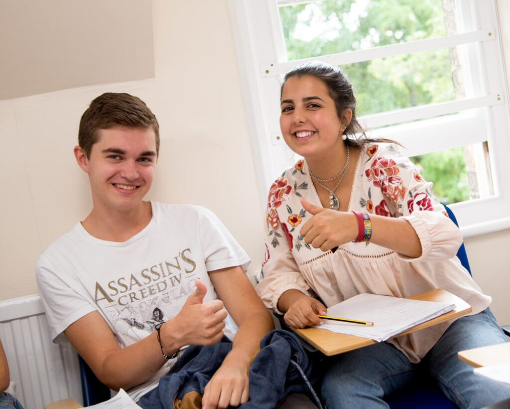 Two students sitting in a classroom smiling with their thumbs up