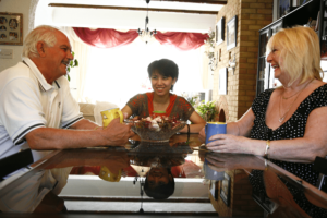 A student sits at the table with her host family.