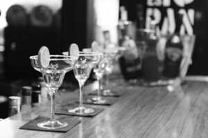 black and white photo of cocktail classes on a bar